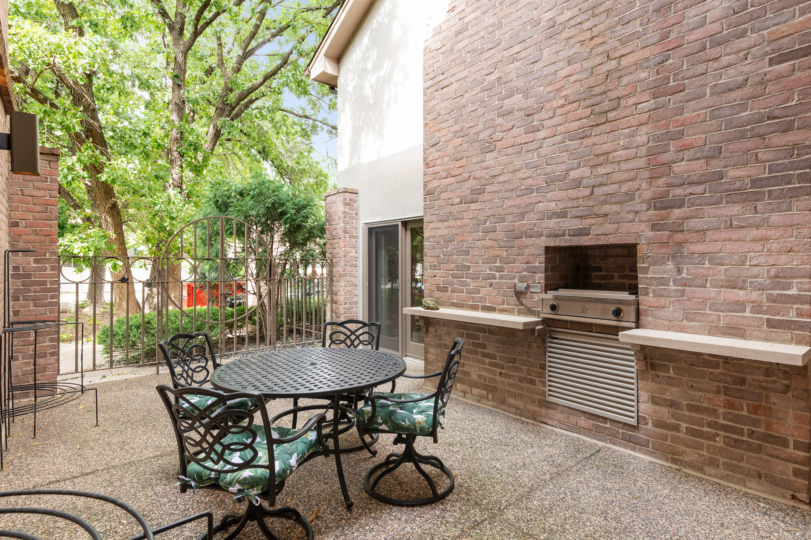 Private gated courtyard patio with a built-in gas grill