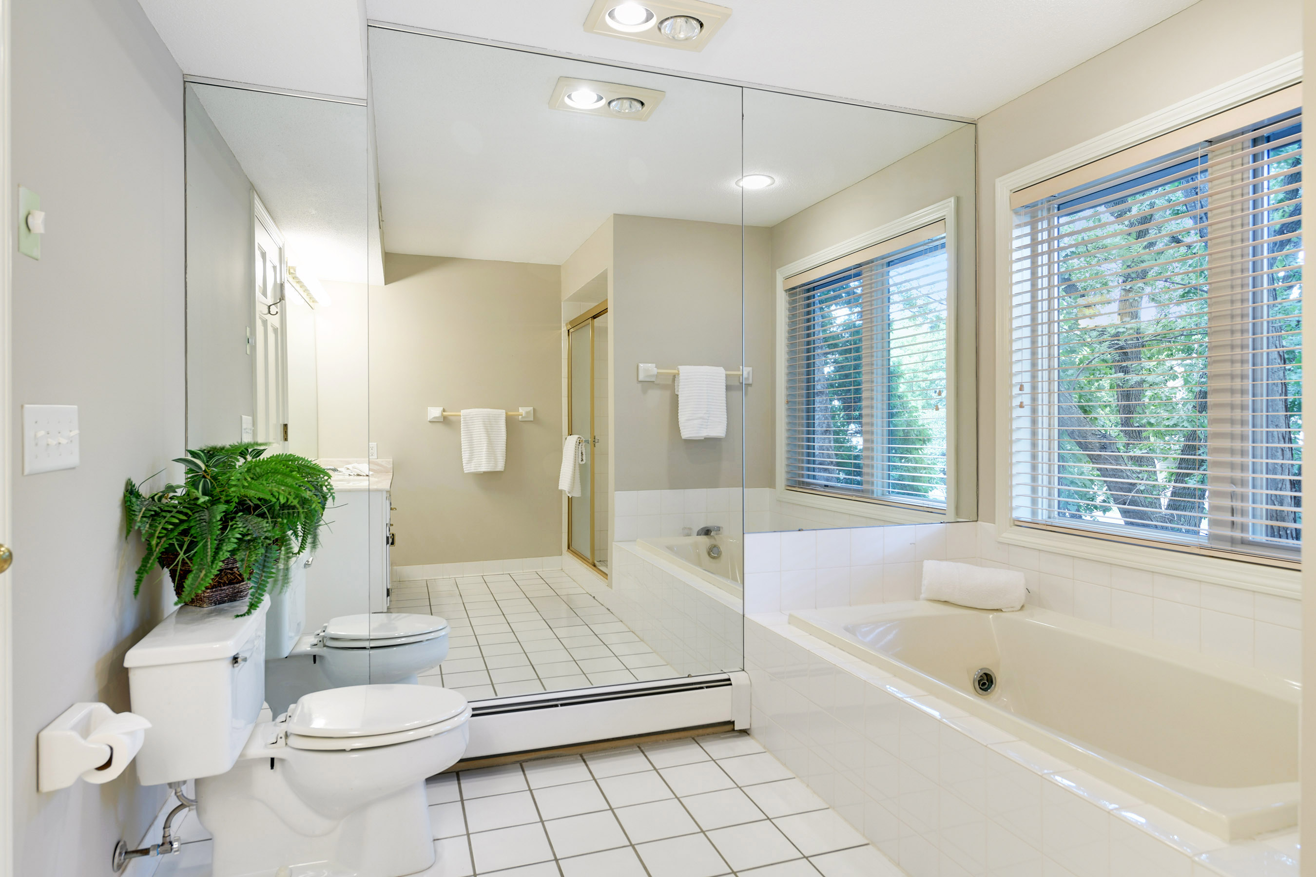 White tile bath with a separate shower and jetted tub
