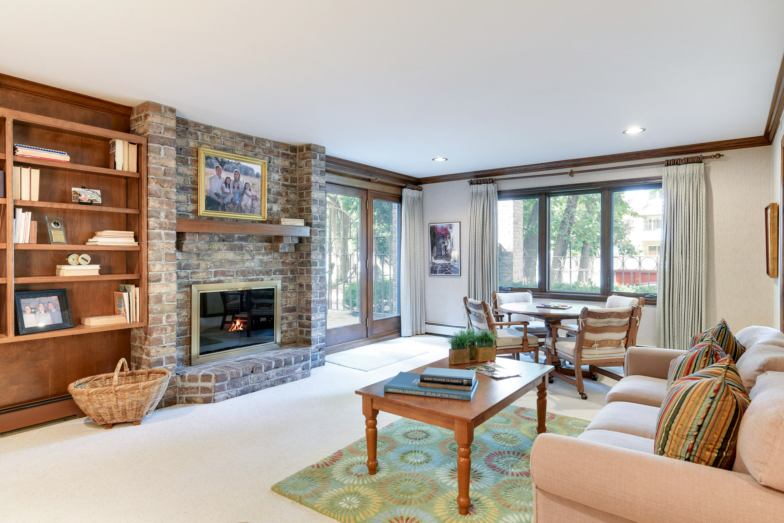 Main floor family room is a great place for daily living featuring a brick gas log fireplace, a built-in bar and a terrace door to the patio.